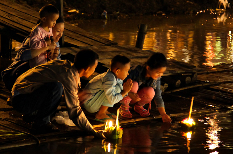 A family float candles in paper boats during the festival of Loi Krathong. Credit: John Shedrick. Licensed under CC BY 2.0