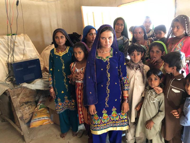 Women and children of the village of the village of Murid Khoso in Sindh province's Sujawal district, Pakistan, pose beside their prized possession -- battery hub with in-built charge controller, December 26, 2017. Thomson Reuters Foundation/Zofeen Ebrahim