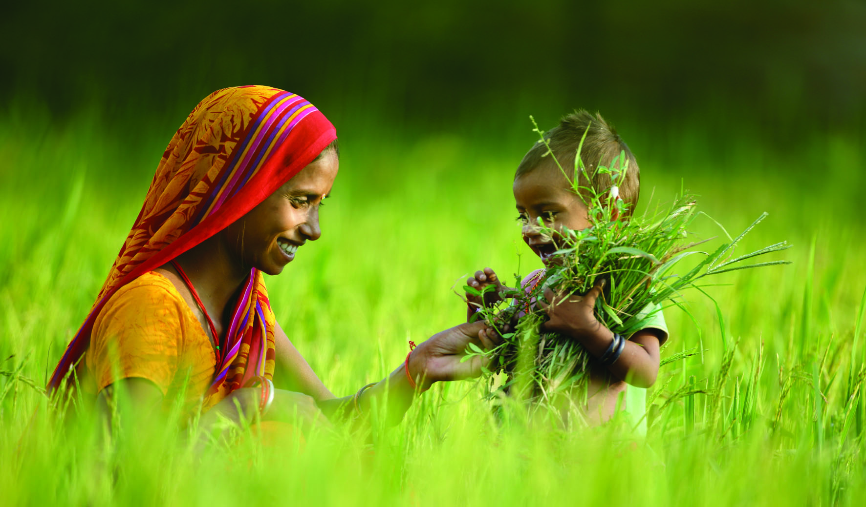 Mom and baby laughing at the rice field. Photo credit: GEAG