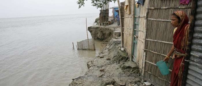 In this 2008 file photo, a woman looks at the River Padma from her house under threat from erosion of the river in Shariatpur, Bangladesh. REUTERS/Andrew Biraj